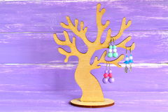 A small decorative tree to store earrings. How to organize earrings. How to store bijouterie at home. Earring holder. Wooden organizer for jewelry. Lifehack Stock Photo