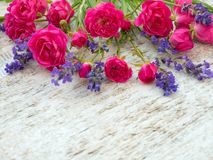 Small deep pink roses and provence lavender bouquet. On the rough white painted background royalty free stock image