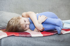 Small defenseless child huddled on the sofa Royalty Free Stock Photography