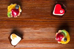 Small delicious cakes on the wood background. Small delicious fruit cakes on the wood background Royalty Free Stock Photography