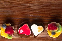 Small delicious fruit cakes on the wood background. Four small delicious fruit cakes , heart shape, on the wood background Royalty Free Stock Photos