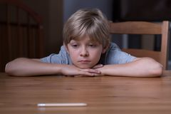 Small depressed boy. Image of small depressed boy laying his head on hands Royalty Free Stock Photo