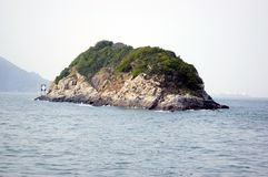 Small deserted island in Hongkong. Small deserted island near Aberdeen harbour in Hongkong covered with some rocks and bushes Stock Images