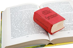 Small dictionary. The small red dictionary lays on the opened book Stock Photo