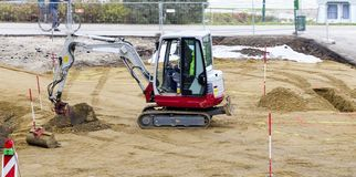 Small digger. Working on a sandy road construction zone at Tulln, Austria stock photography