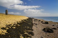 Yellow dike. Small dike in the Netherlands, made of yellow bricks and grown with seaweed stock image