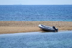 Small dinghy at a lonely beach. Stock Photos