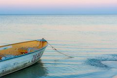 Small dingy or tinny moored at the beach at dusk with waves lapping at the shore. A small dingy or tinny moored at the beach at dusk with waves lapping at the stock photo