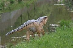 small Dinosaur. Small dinosaur walking near the river Stock Photo