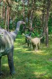 Small diplodocus dinosaurs statues. In a forest Stock Photos