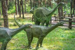 Small diplodocus dinosaurs statues. In a forest Royalty Free Stock Images