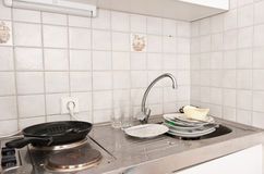 Small dirty kitchen. A small and dirty kitchen with a sink full of dishes stock photo