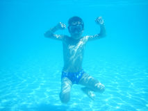 Small diver boy. In the blue water Stock Images