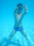 Small diver boy. In the blue water Stock Image