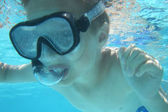 Small diver boy. In the blue water Royalty Free Stock Image