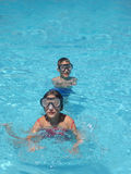 Small diver boy and girl. In the blue water Stock Image