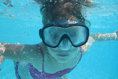 Small diver girl. In the blue water Royalty Free Stock Photos