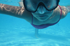 Small diver girl. In the blue water Stock Photography