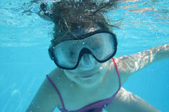 Small diver girl. In the blue water Stock Images