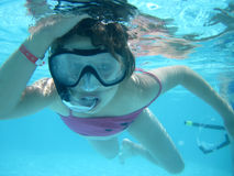Small diver girl. In the blue water Stock Photo