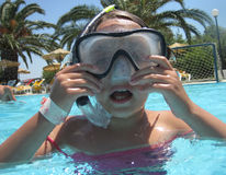Small diver girl. In the blue water Royalty Free Stock Photography