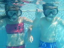 Small diver girl and boy. In the blue water Royalty Free Stock Photography