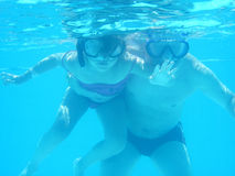 Small diver girl and her father. In the blue water Royalty Free Stock Photos