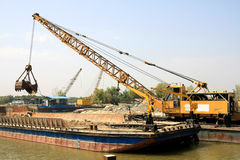 Small dock crane. Fluvial dock crane unloading construction materials from a barge Royalty Free Stock Photo