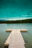 Small dock II. Small dock under a turquoise sky on a lonely lake Stock Images