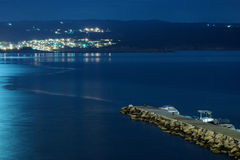 Small dock at night with town on Krk island at Adriatic sea Royalty Free Stock Image