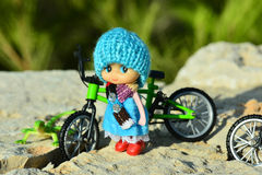 Small doll and bike Royalty Free Stock Image