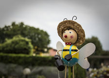 A small doll with wings and a bucket. In hand seems to fly in the blurry background of a summer garden Stock Image