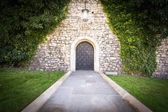 Small door at stone wall of old castle. Royalty Free Stock Photo