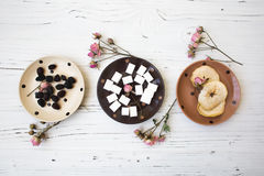 Small doted plates on the white wooden table with sweet things. Three small doted plates on the white wooden table with sugar, dried fruits stock photos