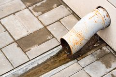 Small drain water pipe and pavement outdoors. Close up end of drain water pipe on street with pavement tile background Royalty Free Stock Photo