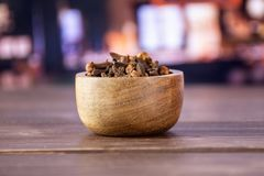 Small dried cloves spice with restaurant. Lot of whole small dried cloves spice with wooden bowl with restaurant in background royalty free stock photos