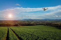 Small drone above the field. Small drone is flying above the large green field royalty free stock photo