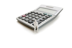 A small dummy figure sitting on a calculator over white background Stock Photos