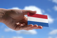 Small Dutch flag. Against beautiful sky with cumulus clouds Royalty Free Stock Images
