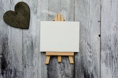 Small easel with a blank canvas over white and dark wooden heart. Old wooden background and big copy space for your sign stock image