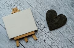 Small easel with a blank canvas over white and dark wooden heart. Old wooden background and big copy space for your sign stock photography