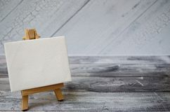 Small easel with a blank canvas over white. Old wooden background and big copy space for your sign and text stock images