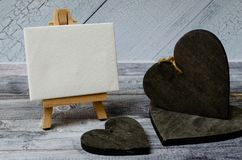 Small easel with a blank canvas over white and three dark wooden hearts. Old wooden background and big copy space for royalty free stock photos