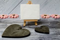 Small easel with a blank canvas over white, two dark wooden hearts and four pink wooden flowers. Old wooden background stock photo