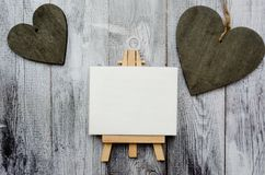 Small easel with a blank canvas over white and two dark wooden hearts. Old wooden background and big copy space for your royalty free stock photos