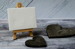Small easel with a blank canvas over white and two dark wooden hearts. Old wooden background and big copy space for your stock photography