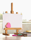 Small easel and school supplies. Small blank easel with heart shaped stickers and other school supplies on desk Stock Photo