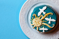 Small easter blue cake with yellow sun and white doves in the white plate. Blue background. Stock Photography