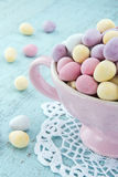 Small easter eggs on a wooden table. Small easter eggs in a pink cup on light blue wooden table Royalty Free Stock Photography