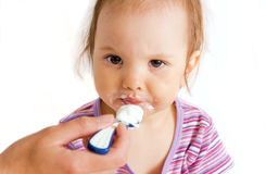 Small eating girl. Small angry girl is fed by her mother Royalty Free Stock Photography